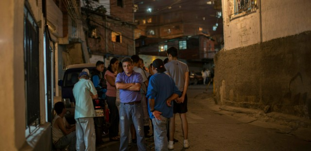 "Neighbors wait to receive bags with subsidized food distributed under a government program named ""CLAP,"" in the Catia district of Caracas, Venezuela, Thursday, Jan. 31, 2019. An independent U.N. human rights monitor says economic sanctions are compounding a ""grave crisis"" in Venezuela."