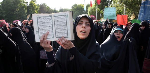 "An Iranian woman chants slogan as she holds a copy of the Quran, Islam's holy book, in a demonstration of religious citizens to protest against non-observance of Islamic dress code in northern Tehran, Iran, Saturday, July 12, 2014. Some 500 people attended the rally calling upon officials to take harsher actions against women with loose headscarves and tight clothes. As the summer has approached and weather gets hot, many women wear colorful, more comfortable clothes and loose headscarves, a fashion that some traditional religious people and hard-liners refer to ""bad hijab"" and view as an imported Western culture. Under the country's current Islamic regulations, women should cover themselves head to toe, with their faces allowed to show. (AP Photo/Vahid Salemi)"