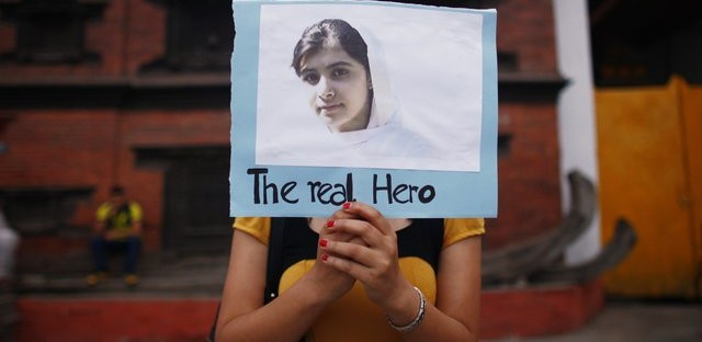 Nepalese student holds picture of Malala Yousafzai at candlelight vigil