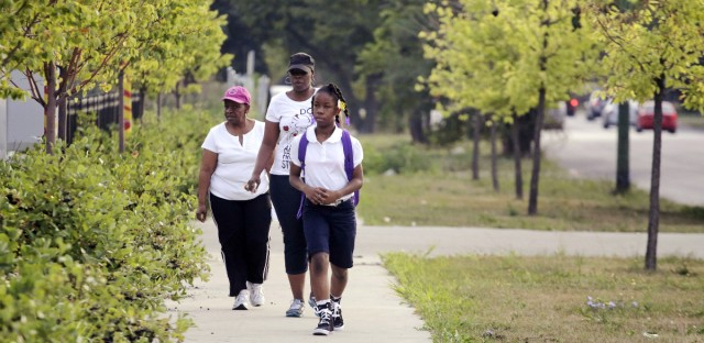 Chicago closed a record 50 schools in 2013, affecting 11,000 children from those schools. Kayla Porter, 9, walks with her grandmother and mother to her new school on the South Side after the school Kayla had attended the previous school year was closed.