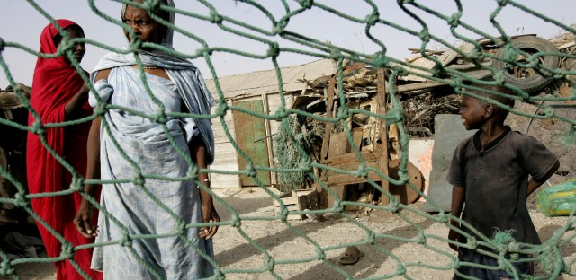 People stand outside their home in a poor neighborhood of Nouakchott, Mauritania in this June 26, 2006 file photo. The northwest African nation of Mauritania passed a law late Wednesday, Aug. 8, 2007, that promises jail time for people who keep slaves, a monumental step in the country's attempt to route out the long-standing practice.