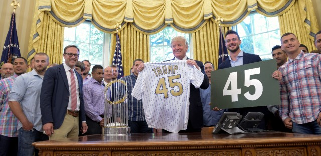 """President Donald Trump meets with members of the 2016 World Series Champions Chicago Cubs, Wednesday, June 28, 2017, in the Oval Office of the White House in Washington. Cubs third baseman Kris Bryant holds the other """"45"""" sign."""