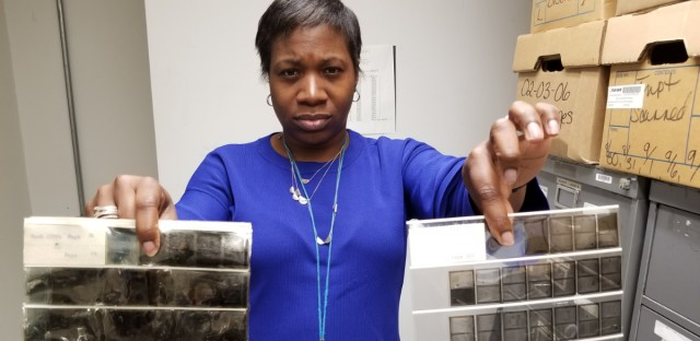 Rachel Jordan, director of informational retrieval at the Cook County Recorder of Deeds office, holds up microfilm infected with vinegar syndrome next to a healthier one.