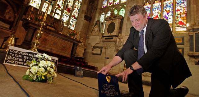 """In this Monday, Sept. 21, 2009 file photo, Head Verger Jon Ormrod tends to the grave of William Shakespeare in the Chancel of Holy Trinity Church in Stratford Upon Avon, England. Archeologists who scanned the grave of William Shakespeare say they have made a startling discovery: His skull appears to be missing. The researchers used ground-penetrating radar to explore beneath the playwright's tomb in Stratford-upon-Avon's Holy Trinity Church. Kevin Colls, who led the study, said the team found """"an odd disturbance at the head end."""" He said Thursday, March 24, 2016 the finding lends support to a claim that the Bard's skull was stolen by grave-robbers in the 18th century."""