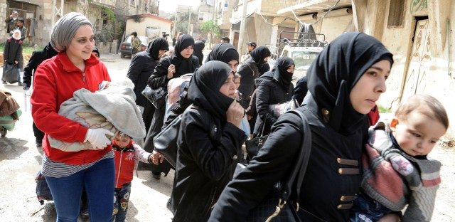 This photo released by the Syrian official news agency SANA, shows civilians carrying their belongings as they left the rebel-held suburb of Douma, east of the capital Damascus, Syria, Saturday, March. 24, 2018.