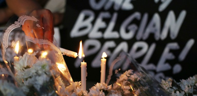 A Filipino activist lights candles among flowers offered for victims of Brussels attacks beside a condolence sign in suburban Quezon city, north of Manila, Philippines to condemn the latest attacks Wednesday, March 23, 2016. Philippine President Benigno Aquino III has ordered an extra tightening of security in all airports, seaports and public transport terminals across the country following explosions in Brussels that killed many people.