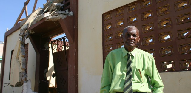 Church leader Nerjuste Louis Sony stands in front of his church, left roofless by the hurricane.