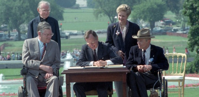 President George H.W. Bush signs the Americans with Disabilities Act during a ceremony on the South Lawn of the White House on July 26, 1990. (Barry Thumma/AP)