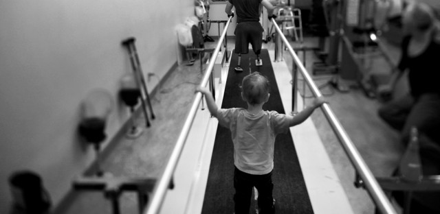 """Liam, 2, accompanies his dad, Jake Romo, during rehab at the Naval Medical Center in San Diego. Romo, 22, lost both his legs while serving with the 3rd Battalion, 5th Marines, in Sangin, Afghanistan. From the story """"For Wounded Marines, The Long, Hard Road Of Rehab,"""" 2011."""