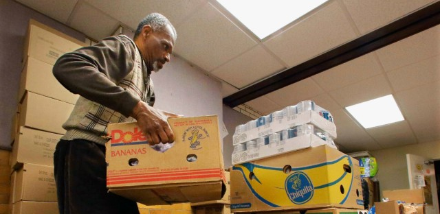 In this Jan. 15, 2013 file photo, Fred Drake helps prepare food supplies to be distributed to people and families in need at the Grace Lutheran Church Food Pantry in Springfield.