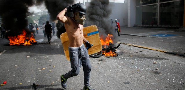 An anti-government demonstrator walks past two National Guard soldiers' motorcycles that were set on fire by protesters when the soldiers ran from their bikes after falling during clashes with protesters in Caracas, Venezuela, Wednesday, May 31, 2017. Protesters have flooded the streets of Venezuela for months, demanding new elections and faulting President Nicolas Maduro's leadership for the country's triple-digit inflation, surging crime rates, and dire shortages of food and medicine.