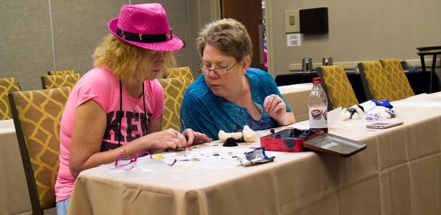 Kristine Barbie Schamberger, left—who adopted her middle name when she married her husband, Ken— consults with her friend DiAnn Richardson in a crafting workshop.
