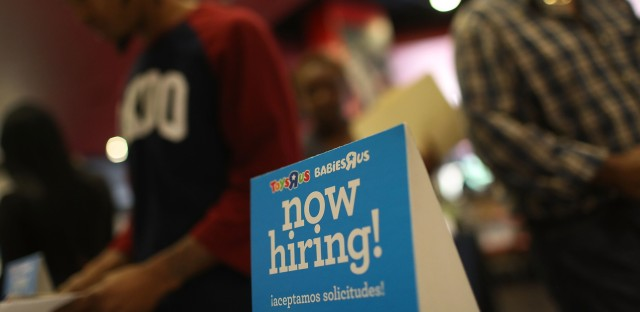 "A ""now hiring"" sign is seen at the Toys R Us booth during the JobNewsUSA job fair at the BB&T Center in Sunrise, Fla., on Nov. 15."