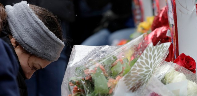 One of victim Vicente Juarez's daughter Diana Juarez cries at a makeshift memorial Sunday, Feb. 17, 2019, in Aurora, Ill., near Henry Pratt Co. manufacturing company where several were killed on Friday.
