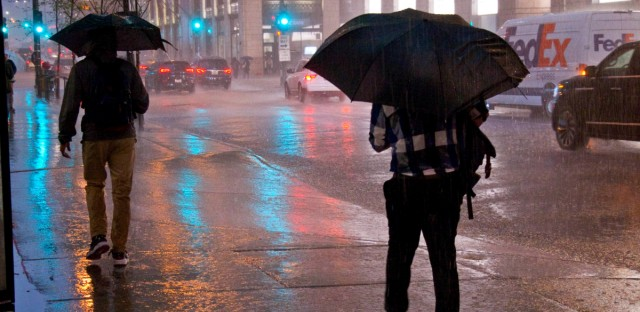 Pedestrians are caught in a heavy downpour and thunderstorm in downtown Chicago in this May 14, 2018, file photo. Experts say the unusual spring weather in Illinois and the region in 2019 is the wettest spring ever recorded since the late 1800s.