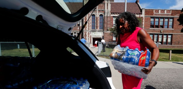 Ivy Bailey, Detroit Federation of Teachers president helps carry bottled water at Noble School in Detroit, Tuesday, Sept. 4, 2018. Some 50,000 Detroit public school students will start the school year Tuesday by drinking water from coolers, not fountains, after the discovery of elevated levels of lead or copper — the latest setback in a state already dealing with the consequences of contaminated tap water in Flint and other communities.
