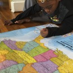 Brandon Kirksey, 8, studies a map of the U.S. in the living room of his family's Detroit home.