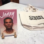"A copy of Jarry, a gay men's food magazine, next to tote bags that read ""Cheers Queers."""