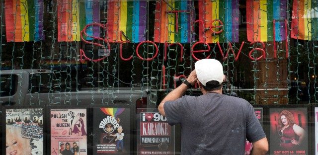 A man looks through a window into the Stonewall Inn, Wednesday, Oct. 11, 2017, in New York. The neighborhood around the bar was the site of riotous protests in 1969 after gay patrons of the bar fought back against a police raid. The bar was declared a national monument in 2016.