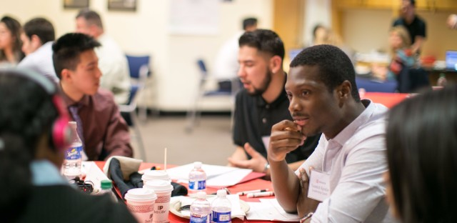 Teacher and consultant Yannick Kpodar (center) engages with students at a Braven event at San Jose State University in California.