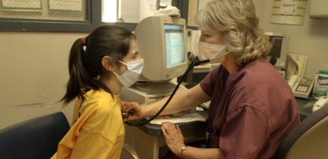 A staff nurse at Advocate Illinois Masonic Medical Center checks a girl's vital signs during a mock bioterrorism drill.