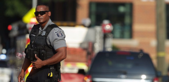 A police officer stands guard near the scene of a shooting Wednesday morning in Alexandria, Va.