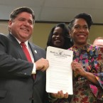 Juliana Stratton and JB pritzker hold up the executive order that created a new criminal justice initiative. (Shannon Heffernan/WBEZ)